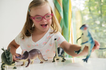 Little Girl With Down Syndrome Playing With Dinosaurs