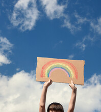 Boy Holding Rainbow Art In Sky