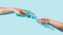 Two Hands With Plastic Bottles.