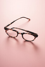 Backlit Tortoise Shell Retro Style Reading Glasses On A Pink Background