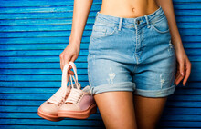 Girl With A Beautiful Figure In Jeans Shorts And Pink Shoes. Girl Hold A Pair Of Shoe. Woman Holding Shoes. Woman Holding A Pair Of Pink Shoes. Girl With A Beautiful Waist In Jeans Shorts