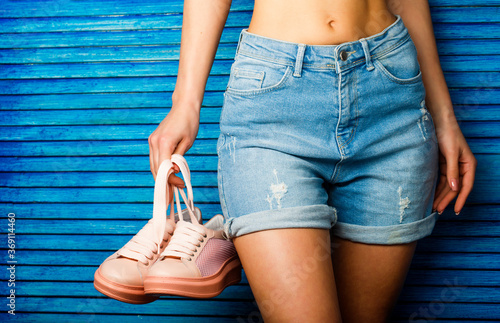 Valokuva Girl with a beautiful figure in jeans shorts and pink shoes