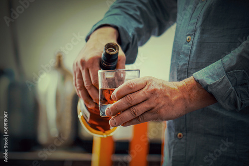 Cuadros en Lienzo Hands of elderly caucasian man with bottle of whiskey on the kitchen