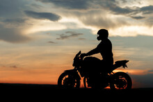 Silhouette Photo Of Biker Driving Motorcycle In Sunset On The On Country Road.