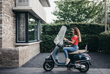 Pretty Teen With Long Hair Sitting On A Vespa Scooter In Front Of A House