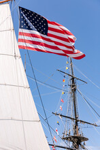 American Flag Waves In The Sky While Hanging From The Mast Of A Sail Boat.