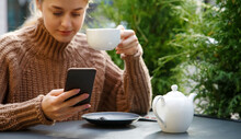 Smiling Adult Woman Focusing On Screen And Using Smartphone While Sitting Table And Having Hot Drink