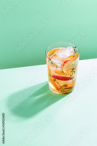 Sparkling cold brew peach tea with thyme in glass on green paper background Fotobehang
