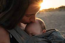 Mother Kissing Baby On Beach