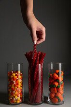 Anonymous Female Hand Reaching For Halloween Candy In Glass Jars.