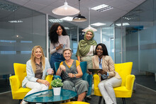 Group Of Business Women Working And Communicating Together In Creative Office.