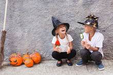 Girl And Boy In Halloween Costumes Having Fun.Brother And Sister Eating Candy For Halloween Outdoor.