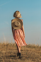 Anonymous Blond Woman Wearing Silk Dress And Straw Sun Hat Outdoors