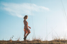 Woman Wearing Sundress Walking In The Grassland Against The Blue Sky