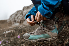 Traveler Tying Shoelaces On Boot In Mountains