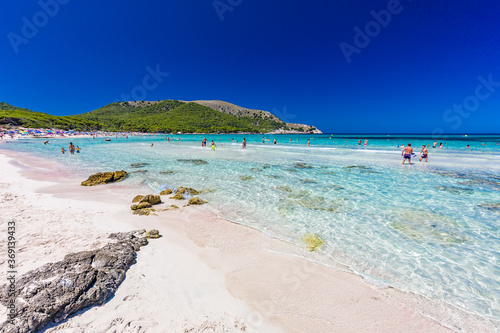 Obraz CALA AGULLA, MALLORCA, SPAIN - 21 July 2020: People enjoying summer on the popular beach on Mallorca,  Balearic Islands. - fototapety do salonu