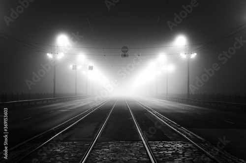 Obraz Tramway track and asphalt road (highway) through the illuminated empty Stone bridge in a thick fog at night. Lanterns close-up. Daugava river, Riga, Latvia. Concept image, black and white, monochrome - fototapety do salonu