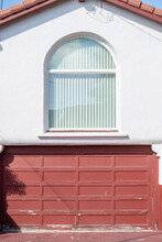 A Close-up Of A White House With A Red Garage And A Big Window