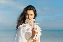 Brunette Woman With Flowers And Foliage At The Beach