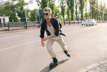 A Man On Roller Skates Quickly Rides In The Backlight With Cars On The Road