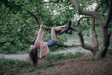 A Girl With Long Black Hair In A Pink Soft Jacket Hangs On Tree Branches Like A Monkey Upside Down