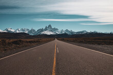 Panoramic Image Of A Long Straight Asphalt Road Leading To Frozen Snowy Mountains In The Horizon And Some Clouds In The Blue Sky. Patagonia, Chile.