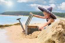 A Treasure Hunt On The Beach. Little Boy Is Playing On The Beach In Summer.