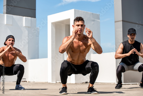 Fotografija Group of fit sports men doing squat bodyweight workout training outdoors on buil