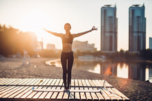Sportswoman Do Yoga At Sunrise