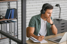 Man With Headphones And Laptop...