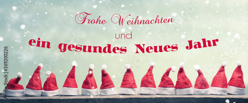 Obraz Hats of Santa in a row on a rustic wooden table, Christmas and New Year greetings in German, panoramic view - fototapety do salonu