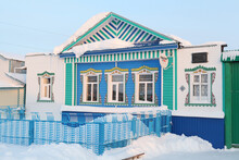 Wooden Rural House With Richly Decorated Traditional National Carved Windows In Russian Village (Ulyanovsk Region, Russia). Russian Folk Style In Wooden Architecture. Building Facade. Snow Winter