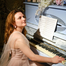 A Young Woman Plays On A Blue Piano In The Rays Of Light. Female Pianist Sits Near A Retro Musical Instrument With Flowers And Candles
