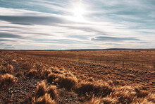 Golden Dry Grass Field And Sun Shinning Behind Faint Clouds During Early Evening. Dry Desert Like Landscape In Patagonia, Chile