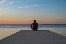 Man In Hoodie And Short Cargo Pants Sitting On The Edge Od Dock And Meditating. Sea Horizon, Island Od Pag, Adriatic Sea, Croatia
