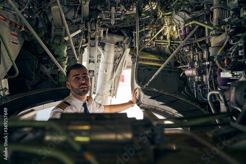 Fényképezés Focused young pilot inspecting an air vehicle