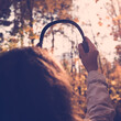canvas print picture - Female with headphones walking on the park listen sounds or music of autumn forest. Concept. Indian summer season