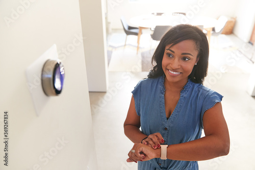 Woman Adjusting Digital Central Heating Thermostat Using Smart Watch At Home Canvas-taulu