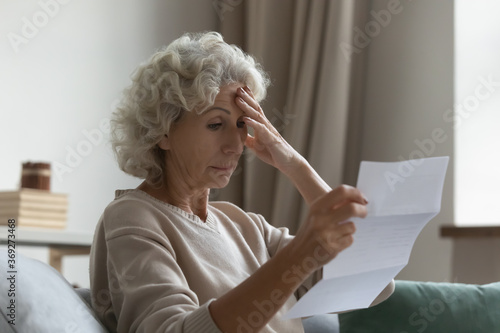 Slika na platnu Disappointed elderly woman sitting on couch in living room feels frustrated by b