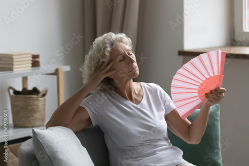 Fotografija Overheated senior woman relax sit on sofa waving orange peach colour fan cool he