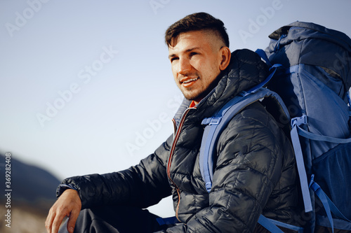 Obraz Portrait of a young caucasian man hiking in the mountains - fototapety do salonu