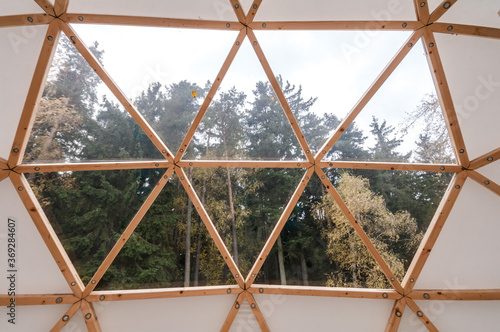 Fotomural Interior of large geodesic wooden dome tent with window and view to forest