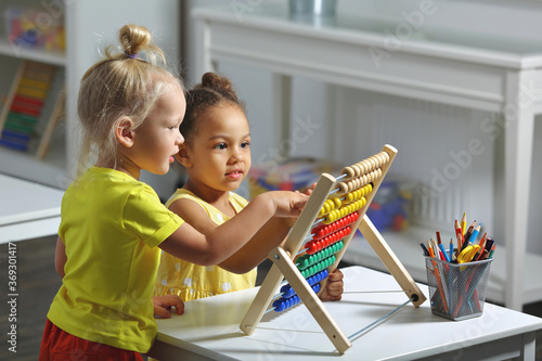 Valokuva children of different races sit together at the table and count on the abacus