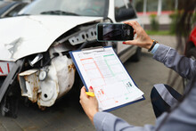 Insurance Agent Takes Pictures Of Crashed Car On His Smartphone And Fills Out The Insurance. Insurance Agent Services Concept
