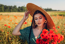 Portrait Of Young Woman Holding Bouquet Of Poppies Flowers Walking In Summer Field. Stylish Girl Wearing Straw Hat