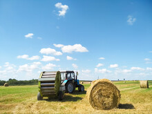 The Tractor Is Harvesting Wheat Hay. Hay Bale. Blank. Rural Life, A Rural Tractor Collects A Sheaf Of Hay On A Green Meadow. Grass, Circle.