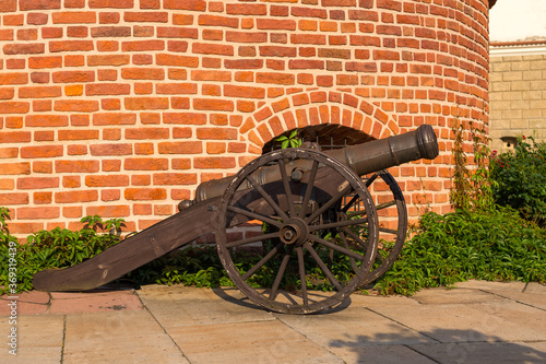 Fotografia Classic old cannon weapon standing by the brick wall
