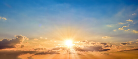 Beautiful blue summer sky with bright sun at sunset as a background