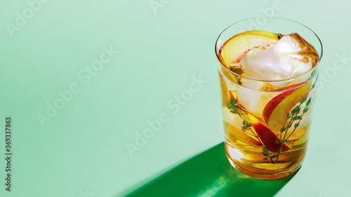 Foto Sparkling cold brew peach tea with thyme in glass on green paper background close-up