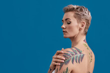 Beauty Portrait Of A Young Attractive Half Naked Tattooed Woman With Perfect Skin Looking Down, Holding Hand On Her Shoulder Isolated Over Blue Background